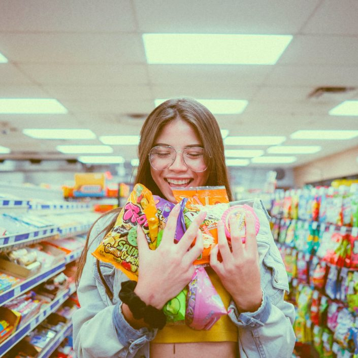 Girl wearing glasses, holding shopping in a supermarket
